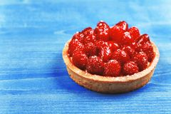 Tartlet with raspberries, top view. Tartlet with custard, fresh glazed raspberries, served on blue wooden surface. Top view Stock Image