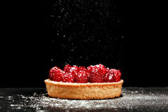 Tartlet with custard and fresh raspberries. Tartlet with custard, fresh glazed aspberries and sieving sugar powder, served on vintage stone surface. Dark rustic Stock Images