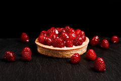 Tartlet with custard and fresh raspberries. Tartlet with custard, fresh glazed raspberries, served on vintage stone surface. Dark rustic style Stock Photo
