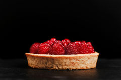 Tartlet with custard and fresh raspberries. Tartlet with custard, fresh glazed raspberries, served on vintage stone surface. Dark rustic style Stock Photos