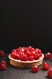 Tartlet with custard and fresh raspberries. Tartlet with custard, fresh glazed raspberries, served on vintage stone surface. Dark rustic style Stock Images
