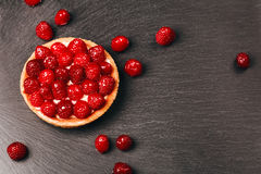 Tartlet with custard and fresh raspberries. Tartlet with custard, fresh glazed raspberries, served on vintage stone surface. Dark rustic style Royalty Free Stock Photography