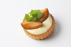 Tartlet filled with vanilla custard plum slices on top on white background Stock Photo