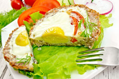 Tartlet meat with egg cut on light board Stock Images