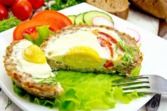 Tartlet meat with egg cut and vegetables on light board Stock Images