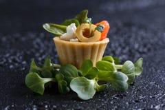 Tartlet med lax- och ostmassaost med mikro-gräsplan på en mörk bakgrund royaltyfri foto