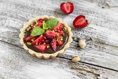 Tartlet mit Schokoladencreme, -erdbeeren und -pistazien Lizenzfreie Stockfotos
