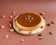 Tartlet nuts do caramelo com as porcas de noz-pecã na placa de madeira Fotografia de Stock