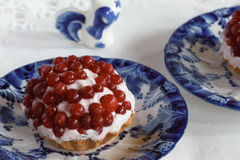 Tartlet with quark and lingonberry and bird. Lingonberry with quark, curd cheese;on white tablecloth, gzhel Royalty Free Stock Images