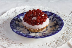 Tartlet with quark and lingonberry. Lingonberry with quark, curd cheese;on white tablecloth, gzhel Royalty Free Stock Image