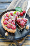 Tartlet with raspberries and fork on the plate. Plate of raspberry tart and fork on old wooden table, selective focus Royalty Free Stock Photo