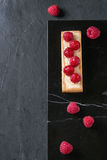 Tartlet with raspberries. Square Tartlet with custard and fresh glazed raspberries, served on black marble board over stone slate surface. Top view Royalty Free Stock Photo