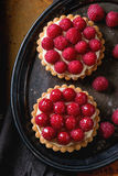 Tartlet with raspberries. Tartlets with custard and fresh ripe raspberries, served on vintage metal tray with textile napkin over rusty metal surface. Dark Stock Image