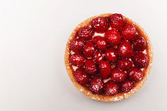 Tartlet with raspberries, top view. Tartlet with custard, fresh glazed raspberries, served on bright surface. Top view Royalty Free Stock Photography