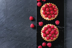 Tartlet with raspberries. Two Tartlets with custard and fresh ripe raspberries, served on black marble board over stone slate surface. With copy space at left Stock Photography