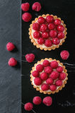 Tartlet with raspberries. Two Tartlets with custard and fresh ripe raspberries, served on black marble board over stone slate surface. Top view royalty free stock images