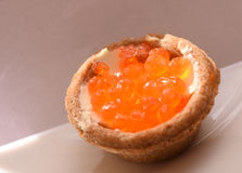 Tartlet with red caviar on a white plate, festive delicacies closeup stock photography