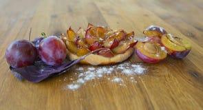 Tartlet van verse pruim, vers pruimfruit op een houten Raad stock foto