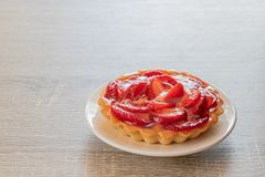 Tartlet with vanilla cream covered with slices of strawberry. royalty free stock images