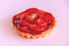 Tartlet with vanilla cream covered with slices of strawberry. stock photo