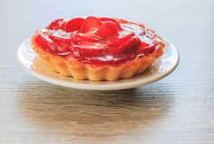 Tartlet with vanilla cream covered with slices of strawberry. stock photography