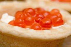 Tartleten med den röda kaviaren och smör på träbrun tabellmakrosikt Arkivbilder