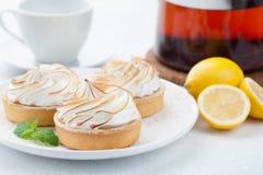 Tartlets λεμονιών με τη μαρέγκα στο εκλεκτής ποιότητας άσπρα πιάτο και το φλυτζάνι του τσαγιού στον πίνακα πετρών Νόστιμος μεταχε στοκ φωτογραφία με δικαίωμα ελεύθερης χρήσης