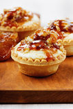 Tartlets με την κρέμα και καρύδια που χύνονται με την καραμέλα Στοκ Φωτογραφίες