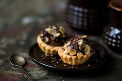 Tartlets με την πλήρωση σοκολάτας που ψεκάζεται με τα αμύγδαλα στοκ εικόνες