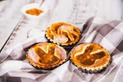 Tartlets взбрызнутые с напудренным сахаром с вареньем персика на белой деревянной предпосылке с полотенцем кухни стоковые фото