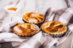 Tartlets взбрызнутые с напудренным сахаром с вареньем персика на белой деревянной предпосылке с полотенцем кухни стоковая фотография