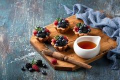 Tartlets грецкого ореха с заварным кремом и ягодами стоковое изображение rf