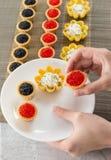 Tartlets заполнили при салат сыра и укропа и икра на бамбуковом placemat и рука выбирая tartlets для того чтобы покрыть Стоковое Изображение RF