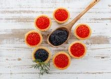 Tartlets заполнили с красной и черной икрой против деревенской деревянной предпосылки Стоковые Фото