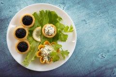 Tartlets заполнили с красным и черным салатом икры и сыра и укропа на белой плите против голубой деревенской деревянной предпосыл Стоковая Фотография