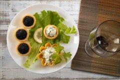 Tartlets заполнили с красным и черным салатом икры и сыра и укропа на белой плите против серебряной деревянной предпосылки Стоковые Изображения RF