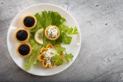Tartlets заполнили с красным и черным салатом икры и сыра и укропа на белой плите против серебряной деревянной предпосылки Стоковое Изображение RF
