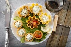 Tartlets заполнили с овощами и салатом сыра и укропа на белых плите и лист против деревенской деревянной предпосылки Стоковая Фотография