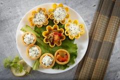 Tartlets заполнили с овощами и салатом сыра и укропа на белых плите и лист против деревенской деревянной предпосылки Стоковые Изображения