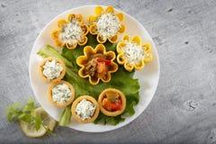 Tartlets заполнили с овощами и салатом сыра и укропа на белых плите и лист против деревенской деревянной предпосылки Стоковое Изображение RF