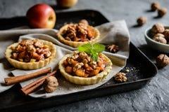 Tartlets плодоовощ заполнили с caramelized частями, циннамоном и грецкими орехами яблока Стоковое Изображение