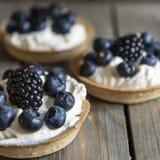 Tartlets свежих фруктов на деревенской деревянной предпосылке кухни Стоковое Изображение RF