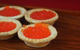 Tartlets с красной икрой на деревянной плите Стоковая Фотография
