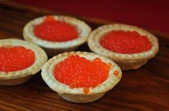 Tartlets с красной икрой на деревянной плите Стоковые Фото