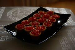 Tartlets с красной икрой на черной плите Стоковые Изображения RF