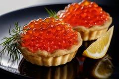 Tartlets с красной икрой на черной предпосылке Стоковые Изображения RF