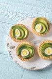 Tartlets с яичками плавленого сыра, авокадоа и триперсток Стоковые Изображения