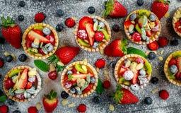 Tartlets ягоды с голубиками, полениками, кивиом, клубниками, миндалиной шелушатся в сахаре замороженности Стоковое Фото