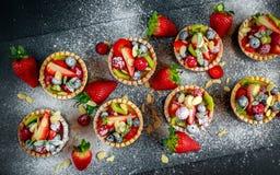 Tartlets ягоды с голубиками, полениками, кивиом, клубниками, миндалиной шелушатся в сахаре замороженности Стоковое Изображение RF