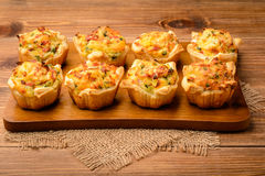 Tartlets baked with mashed potato, cheese, ham and parsley. Royalty Free Stock Photos